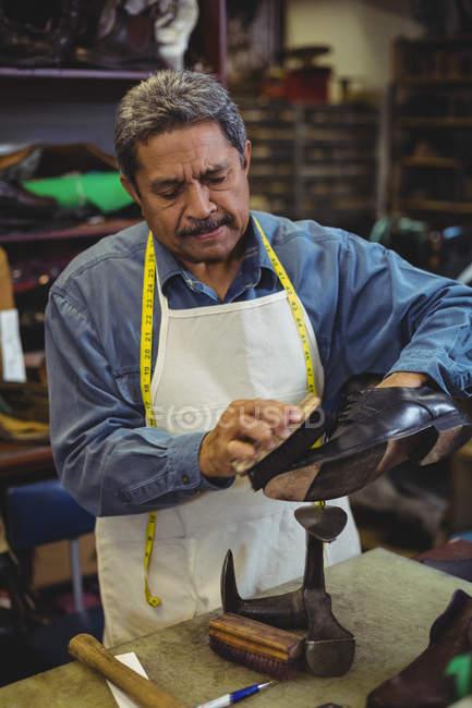 Shoemaker polishing a shoe in workshop — Stock Photo