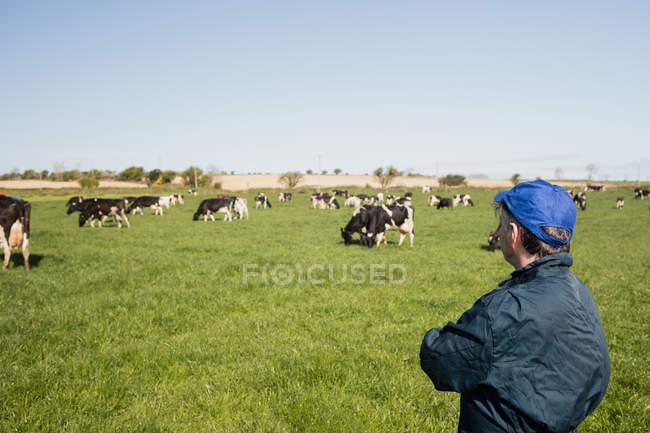 Работник фермы, стоя на травянистые поля против ясного неба — стоковое фото