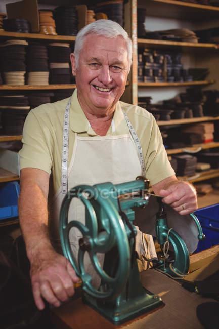 Cheerful shoemaker using sewing machine in workshop — Stock Photo