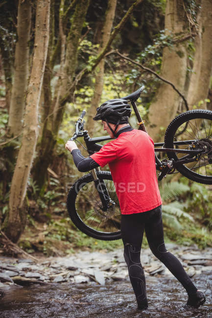 Full length of biker carrying bicycle while crossing stream in forest — Stock Photo