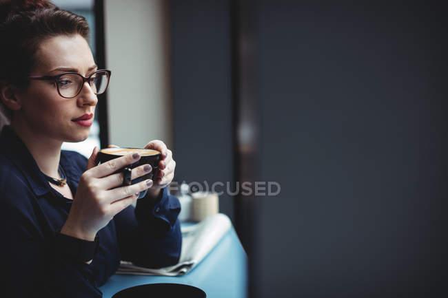 Femme d'affaires réfléchie tenant tasse de café dans le café — Photo de stock