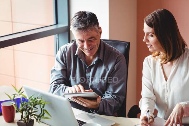 Веселые коллеги смотрят на планшет в офисе — стоковое фото
