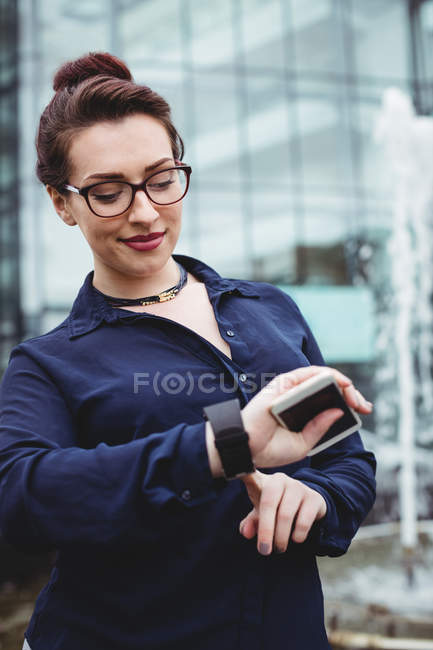 Femme d'affaires souriante vérifiant l'heure à l'extérieur du bâtiment de bureaux — Photo de stock