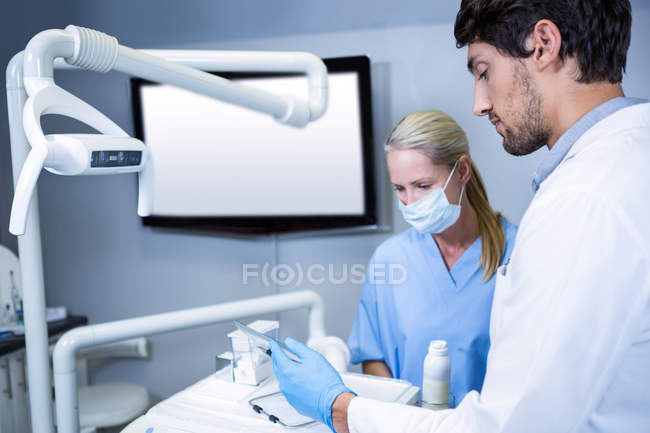 Dentist and dental assistant working together at dental clinic — Stock Photo