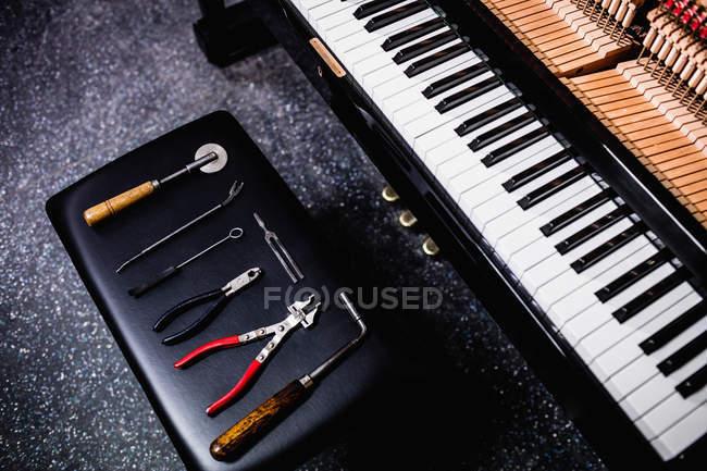 Nahaufnahme von Reparaturwerkzeugen und alter Klaviertastatur — Stockfoto