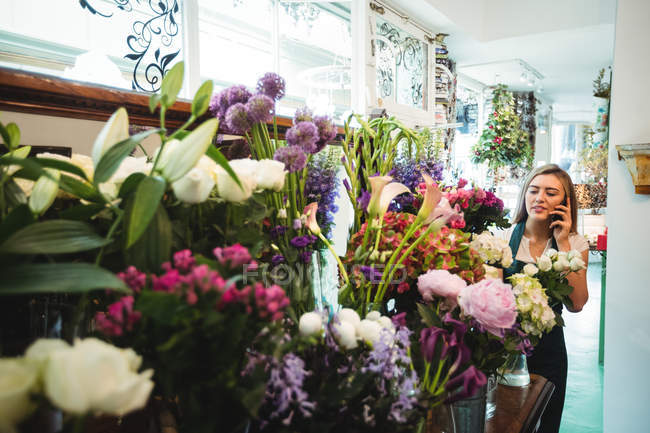 Female florist talking on mobile phone while arranging flowers in the flower shop — Stock Photo