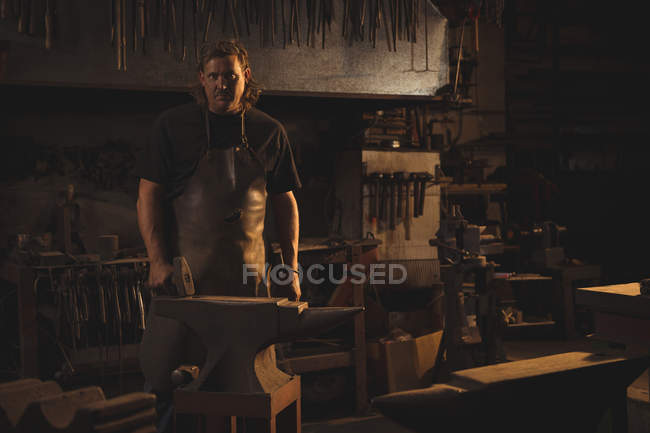 Portrait of blacksmith standing in workshop — Stock Photo