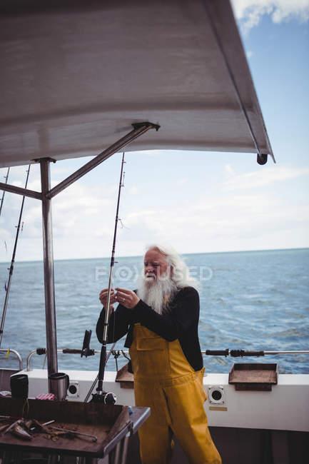 Pescatore regolazione amo da pesca sulla barca da pesca — Foto stock