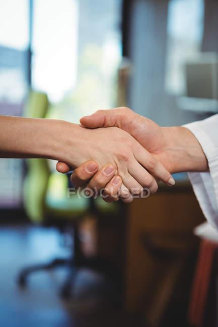 Кадроване зображення фізіотерапевт, потискує руку пацієнтки в клініці — стокове фото