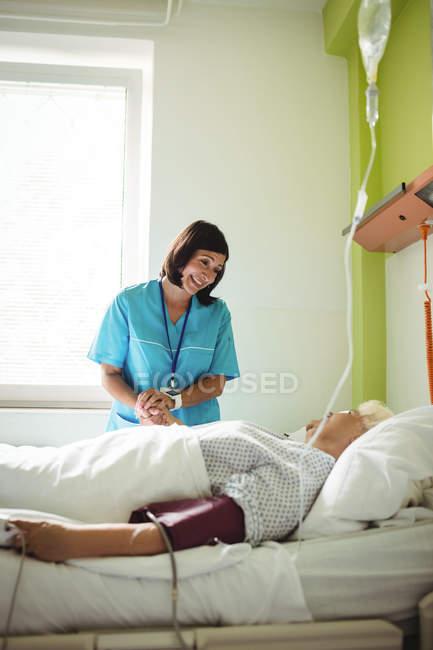 Enfermeira consoladora paciente idoso em enfermaria hospitalar — Fotografia de Stock