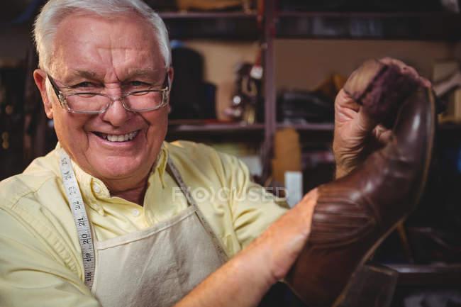 Portrait of shoemaker holding a shoe in workshop — Stock Photo