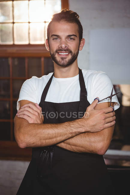Portrait of smiling male hairdresser standing with arms crossed in salon — Stock Photo