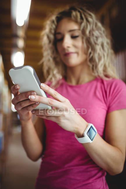 Жінка, що використання мобільного телефону у бібліотеці — стокове фото