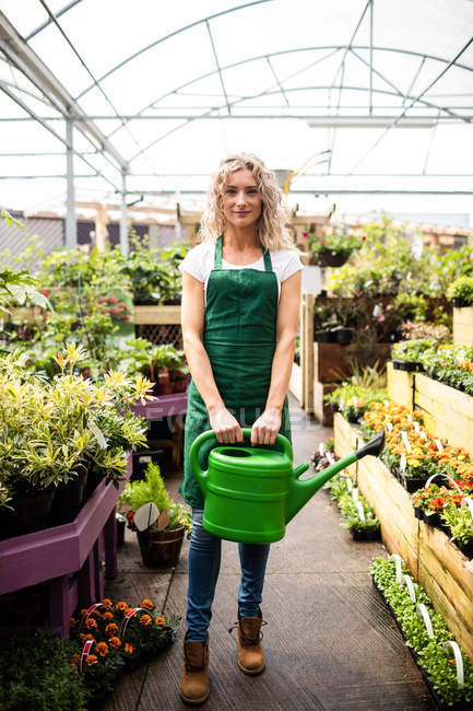 Portrait of female florist holding watering can in garden centre — Stock Photo