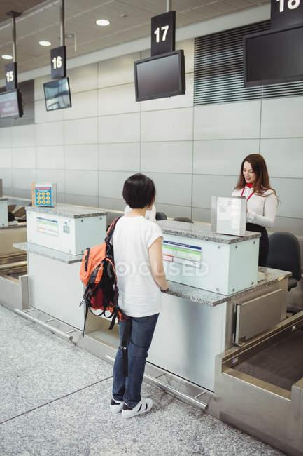 Companhia aérea entrada atendente verificar o passaporte do passageiro no balcão do check-in de aeroporto — Fotografia de Stock