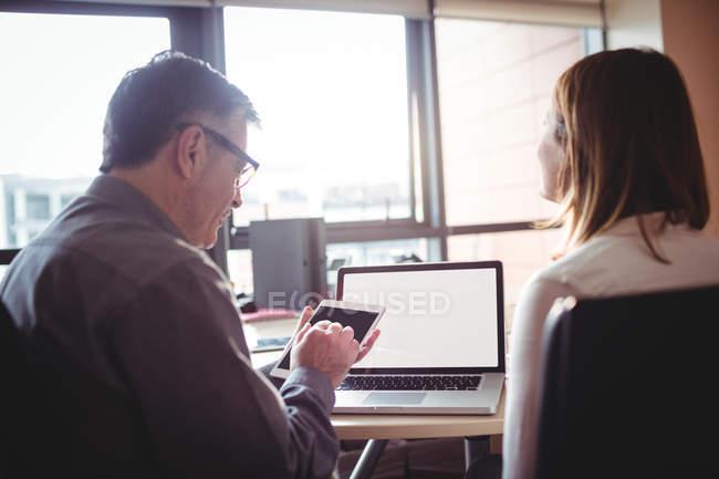 Мужчина и женщина обсуждают за цифровым планшетом в офисе — стоковое фото