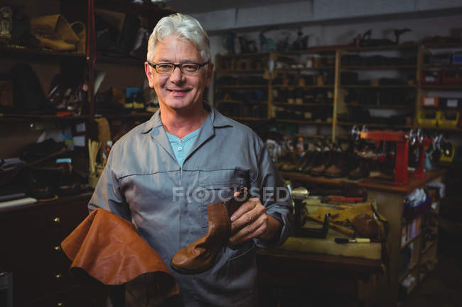 Mature shoemaker holding a boot and piece of material in workshop — Stock Photo