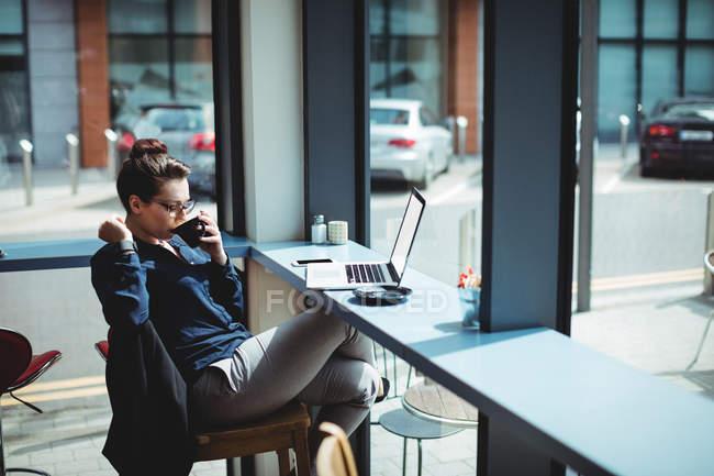 Молодая женщина пьет кофе, сидя на стуле в кафе — стоковое фото