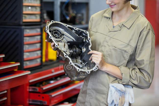 Imagen recortada de mecánico femenino sosteniendo piezas de repuesto en el garaje de reparación - foto de stock