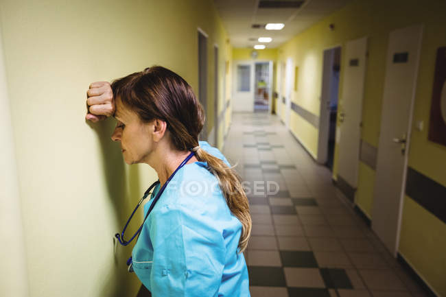 Enfermeira deprimida em pé no corredor hospitalar — Fotografia de Stock
