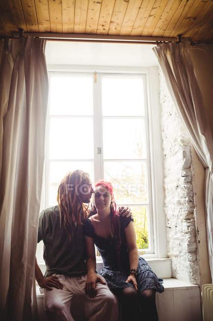 Junge Hipster paar gegen Fenster zu Hause sitzt — Stockfoto