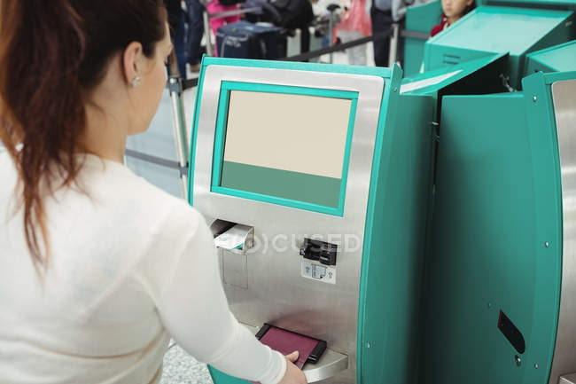 Viaggiatori che utilizzano la macchina self service per il check-in in aeroporto — Foto stock