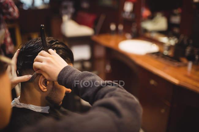 Hombre conseguir su pelo recortado con navaja de afeitar en la peluquería - foto de stock