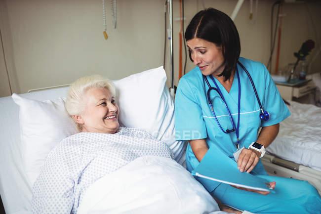 Медсестра взаимодействует со старшим пациентом в больнице — стоковое фото