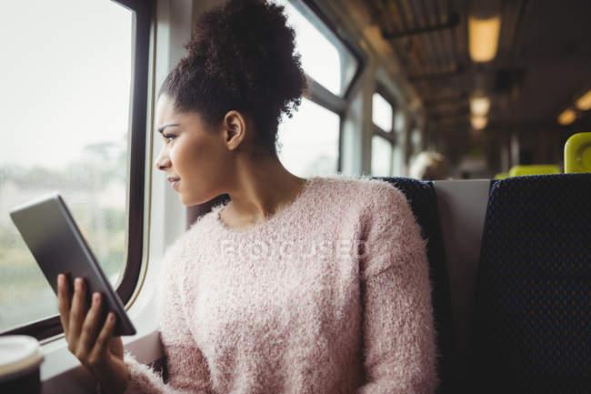 Frau blickt durch Fenster, während sie digitales Tablet im Zug hält — Stockfoto