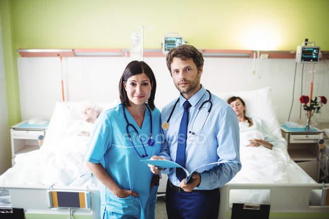 Retrato de médico e enfermeiro na ala do hospital — Fotografia de Stock