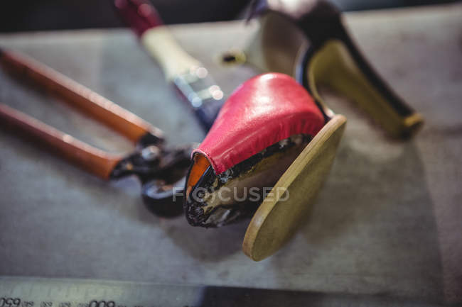 Sapato de salto alto quebrado na mesa na oficina de calçados — Fotografia de Stock