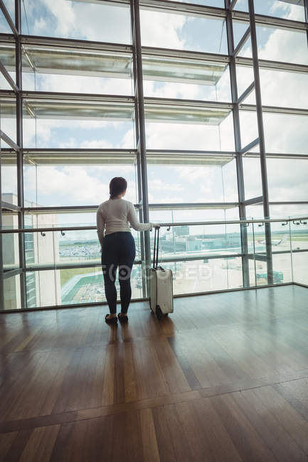 Rear view of businesswoman with luggage looking through glass window at airport — Stock Photo
