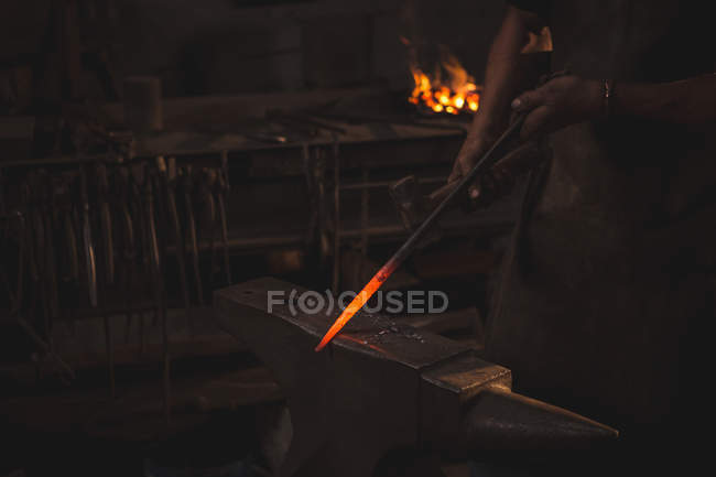 Mid section blacksmith working on hot metal using hammer to shape at work shop — Stock Photo