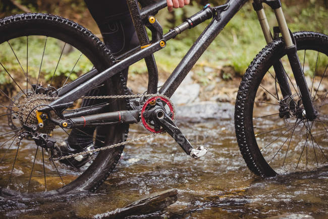 Low section of biker walking with bicycle in stream — Stock Photo