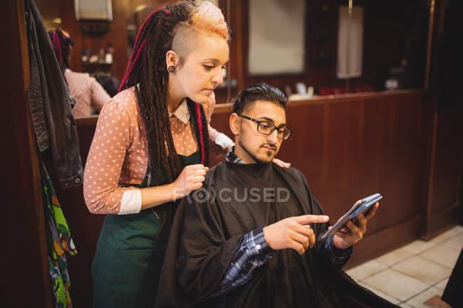 Cliente che mostra tablet digitale al barbiere donna nel negozio di barbiere — Foto stock