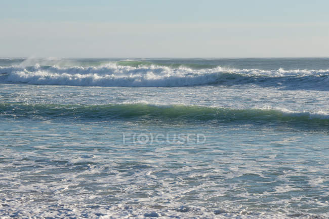 Waves crashing on the beach on a sunny day — view, holiday - Stock