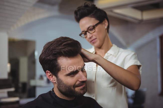 Coiffeur coupe les cheveux du client au salon de coiffure — Photo de stock