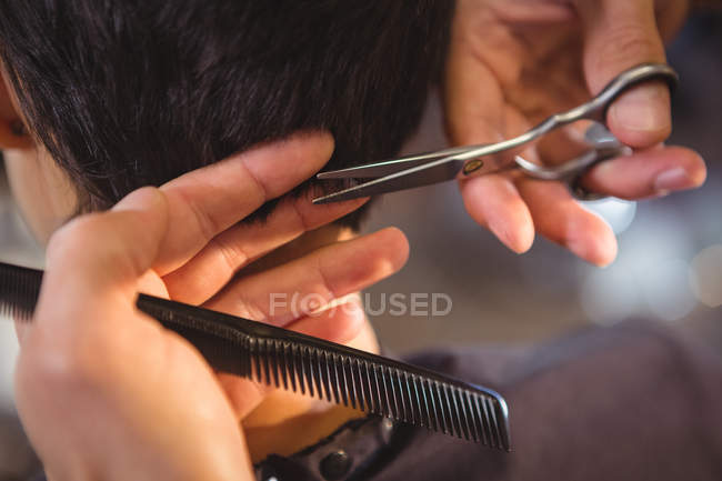 Imagen recortada de la mujer que consigue su pelo recortado en el salón - foto de stock
