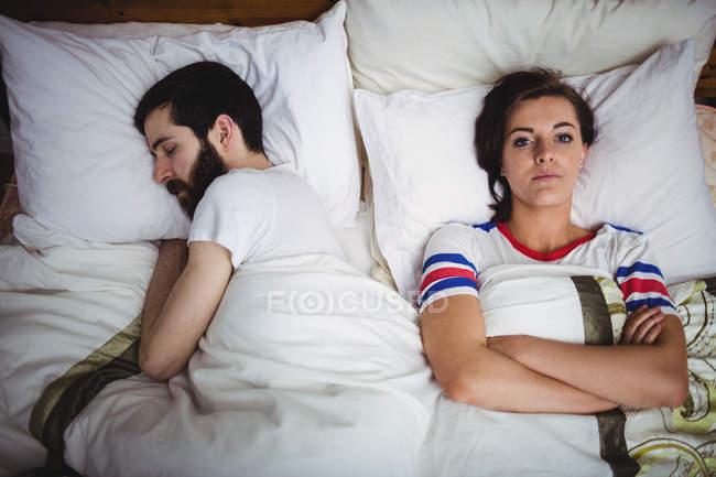 Молодая женщина лежит на кровати со спящим мужчиной в спальне — стоковое фото