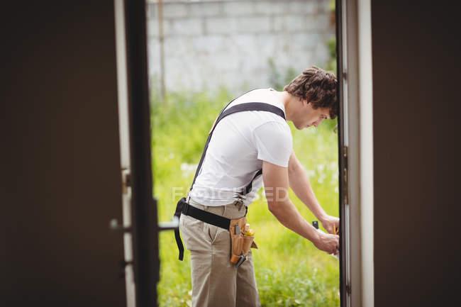 Carpenter measuring door frame outside house — Stock Photo