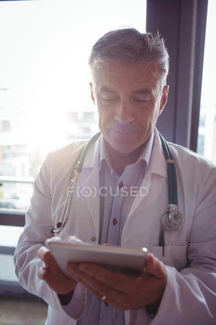 Médico com estetoscópio usando tablet digital no hospital — Fotografia de Stock