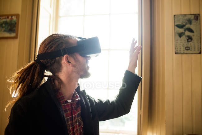 Close-up of hipster gesturing while using virtual reality simulator at home — Stock Photo
