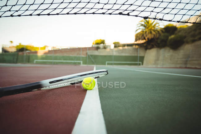 Raqueta de tenis y balón en la línea de centro de corte verde y marrón - foto de stock