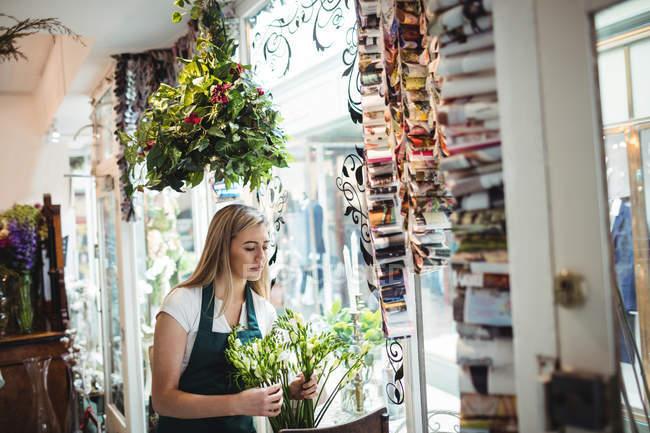 Female florist arranging flower in the flower shop — Stock Photo