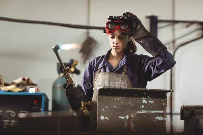 Female welder holding welding torch in workshop — Stock Photo