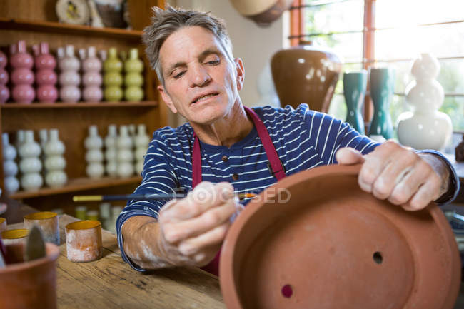 Male potter painting on pot in pottery workshop — Stock Photo