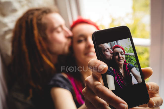Hipster jeune couple prenant selfie par la fenêtre à la maison — Photo de stock