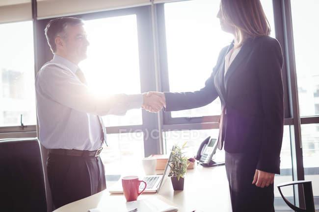 Бізнес-леді і підприємець, потискує руку в офісі — стокове фото