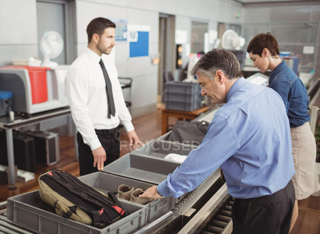 Homem a colocar os sapatos em bandeja para verificação de segurança no aeroporto — Fotografia de Stock