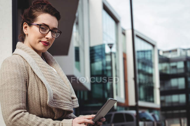 Ritratto di donna con tablet digitale contro edificio moderno — Foto stock